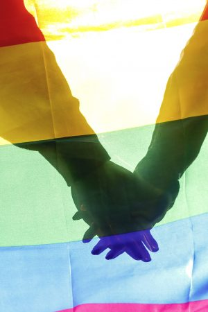 People, homosexuality, same-sex marriage, gay and love concept – close up of happy male gay couple hugging and holding rainbow flag